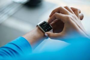 Sintomi da stress da lavoro. Un orologio digitale al polso e l'altra mano che attiva il cronometro di una persona vestita di azzurro di cui si vedono solo le braccia.