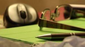 Come-ridurre-lo-stress-al-lavoro-primo-piano-con-penna-occhiali-e-foglio-verde-sul-tavolo