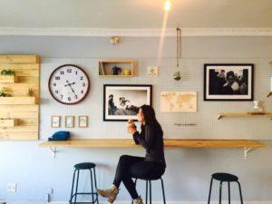 Come-gestire-il-tempo-in-modo-efficace-donna-seduta-su-uno-sgabello-in-pausa-caffe
