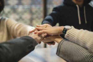 Come-affrontare-e-gestire-i-conflitto-sul-posto-di-lavoro-mani-che-si-incrociano-in-segno-di-alleanza