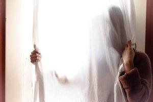 Fargilità al lavoro, donna dietro ad una tenda