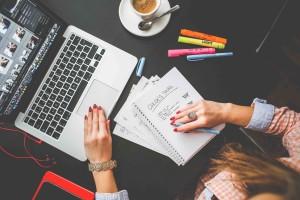 Career coaching - Una donna al tavolo davanti al suo computer che prende appunti nel suo taccuino