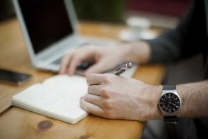 Coaching manageriale - Uomo al tavolo dal lavoro che prende appunti sul suo taccuino