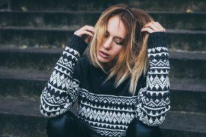 Stress-e-ansia-da-lavoro-come-riconoscerlo-donna-con-maglione-seduta-sui-gradini-con-occhi-chiusi-e-mani-tra-i-capelli