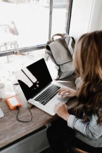 efficacia-della-consulenza-psicologica-online-donna -al-tavolo-che-scrive-al-computer