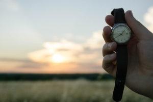 Tecniche per gestire il tempo in maniera efficace, mano che regge orologio da polso sullo sfondo il tramonto
