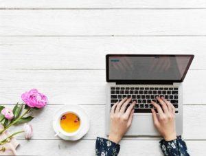 Consulenza-psicologica-online-quando-richiederla-e-come-funziona-mani-di-donna-viste-dall'alto-su-una-tastiera-di-computer
