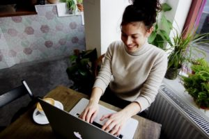 Efficacia-della-psicoterapia-a-distanza-donna-che-sorride-seduta-al-tavolo-col-pc