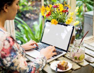 Conciliazione vita e lavoro e work-life balance, donna che lavora al pc in mezzo ai fiori