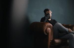 Mobbing e conseguenze sulle relazioni al lavoro. Uomo seduto sul divano