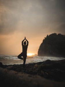 Mobbing stress e rilassamento, donna in posizione yoga e sullo sfondo il tramonto