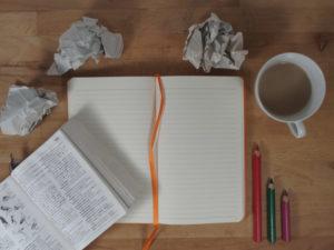 Bilanciamento vita e lavoro Coronavirus, quaderno a righe aperto con tazza di caffè, matite colorate e carte accartocciate
