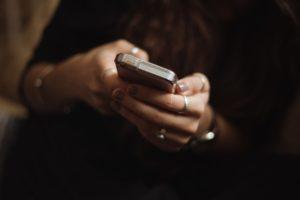 Coronavirus e salute emotiva e psicologica, mani femminili con smartphone