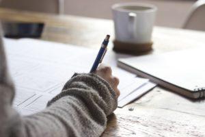 Burnout al lavoro cosa fare: mano sul tavolo che scrive su un foglio con una matita