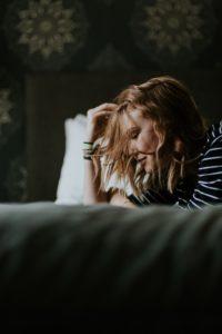 Burnout al lavoro: donna china con la mano sulla fronte.