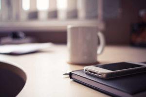 Smart working e capacità da allenare. Tazza, iPhone e agenda appoggiate su un tavolo.